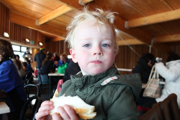 Kid pauses mid-sandwich to complain of hunger.